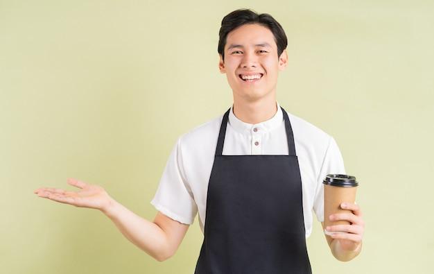 Asiatischer kellner, der pappbecher hält und lächelt