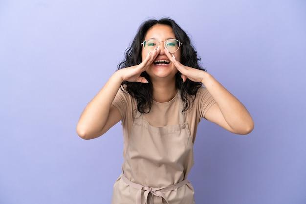 Asiatischer kellner im restaurant isoliert auf violettem hintergrund, der etwas schreit und ankündigt?
