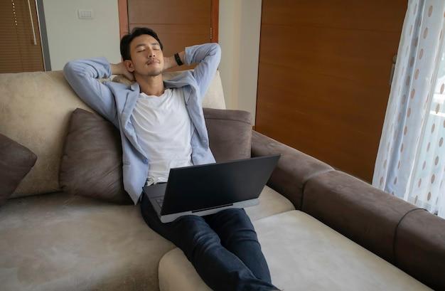 Asiatischer kerl, der auf sofa mit schwarzem notizbuch entspannt.