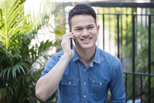 Asiatischer kerl, der ein bequemes kleid spricht auf smartphone trägt