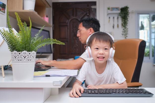 Asiatischer kindergartenjunge, der nahe seinem arbeitenden vater zu hause spielt