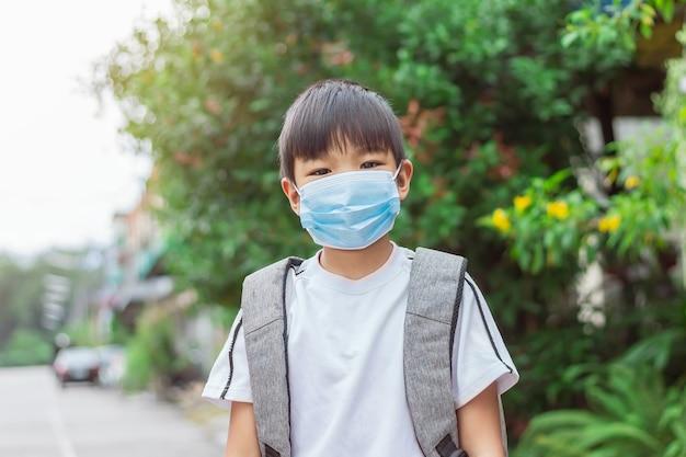 Asiatischer kinderjunge, der eine gesichtsmaske trägt und eine schultasche mitnimmt zurück zur schule und kind