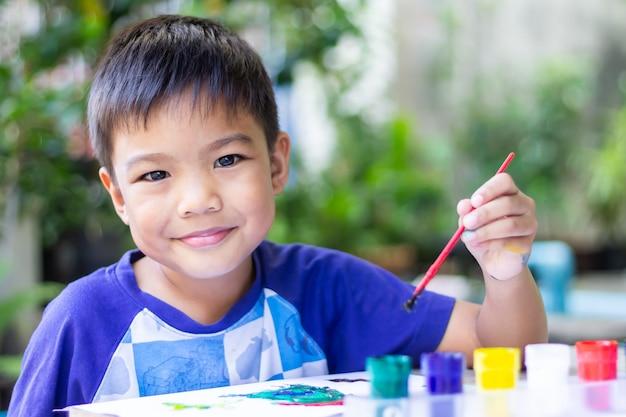 Asiatischer kinderjunge, der farben auf dem papier im raum zeichnet und malt.