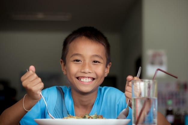 Asiatischer kinderjunge, der gesundes lebensmittel in der kantine oder in der cafeteria isst.