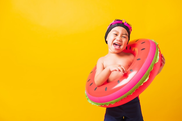 Asiatischer kinderjunge, der schutzbrille und badeanzug mit aufblasbarem strandwassermelonenring trägt