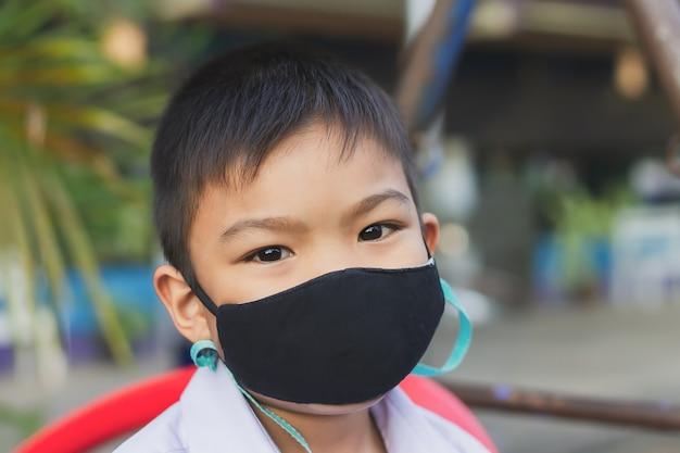 Asiatischer kinderjunge, der stoffmaske trägt