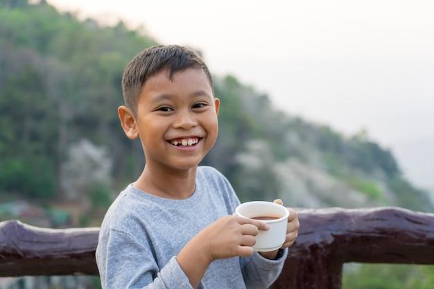 Asiatischer kinderjunge trinkt wasser vom glas. mit blick auf die berge hintergrund