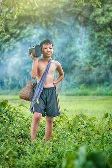 Asiatischer kinderlandwirt, der musik hört