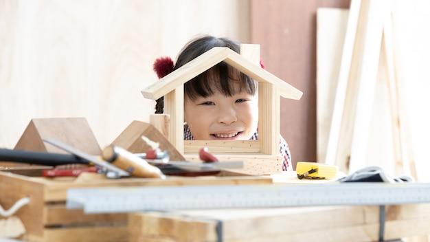 Asiatischer kindermädchentischler, der an holzbearbeitungstabelle in der hauptzimmerei arbeitet