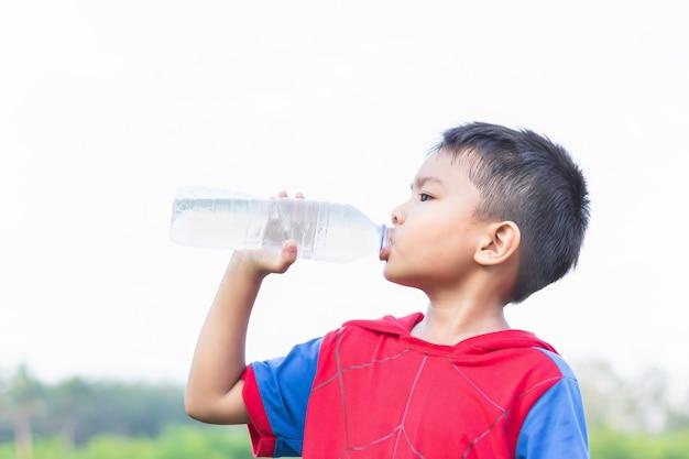 Asiatischer kinderschüler, der etwas wasser durch eine plastikflasche trinkt.