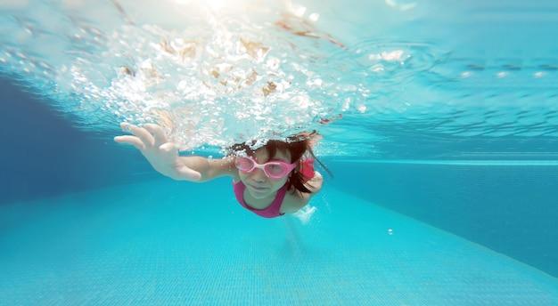 Asiatischer kinderschwimmer übt das schwimmen unter wasser an einem sonnigen tag