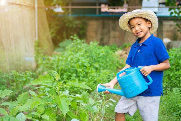 Asiatischer kleiner bauernkindjunge, der das gemüse an der gartenfarm 5 jahre alt des kindes gießt