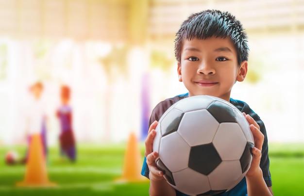 Asiatischer kleiner fußballjunge mit lächeln hält einen fußball mit trainingsgelände backgorund.