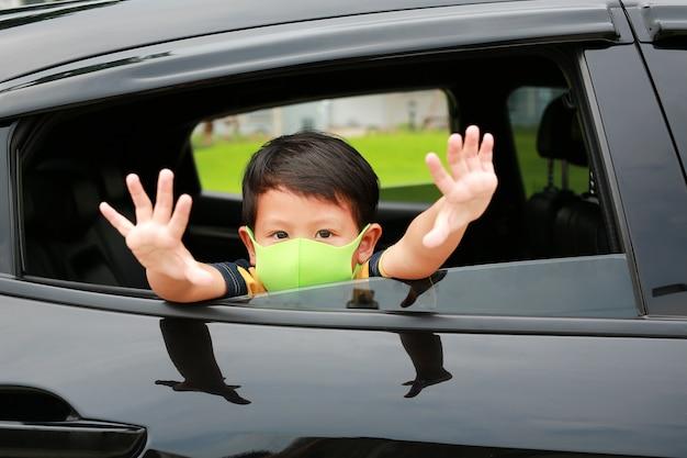 Asiatischer kleiner junge, der eine hygiene-gesichtsmaske trägt, steckt seinen kopf aus dem autofenster mit einer hand-stop-schild-geste während des ausbruchs des coronavirus (covid-19).
