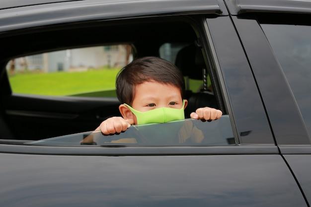 Asiatischer kleiner junge, der eine hygiene-gesichtsmaske trägt, steckt seinen kopf während des ausbruchs des coronavirus (covid-19) aus dem autofenster