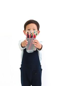 Asiatischer kleiner junge, der einen korb mit buntstiften für sie vor weißem hintergrund gibt. konzentrieren sie sich auf den farbstift in seinen händen