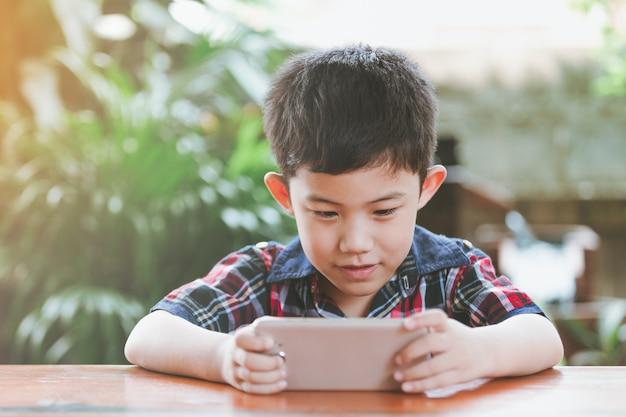 Asiatischer kleiner junge, der online-spiel spielend sitzt