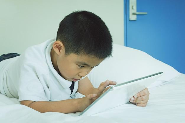 Asiatischer kleiner junge, der tablet-computer im bett verwendet