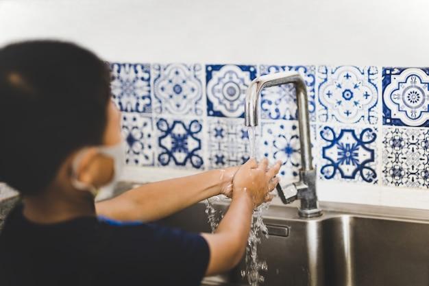 Asiatischer kleiner junge, der während covid-19 mit leitungswasser in der küchenspüle wäscht.