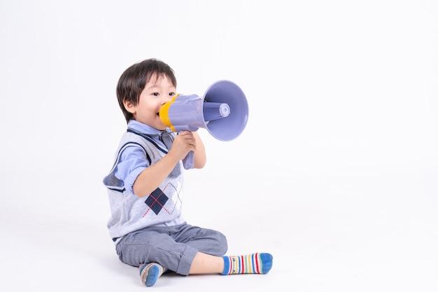 Asiatischer kleiner junge des porträts, der mit glück und freudigem spielen mit megaphon sitzt und lächelt