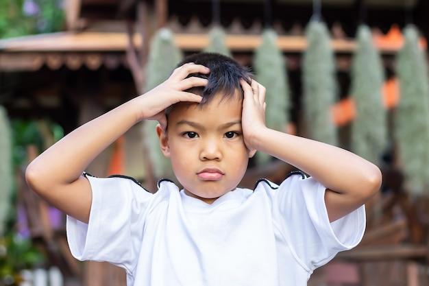 Asiatischer kleiner junge fühlt sich traurig, kopfschmerzen und gestresst.