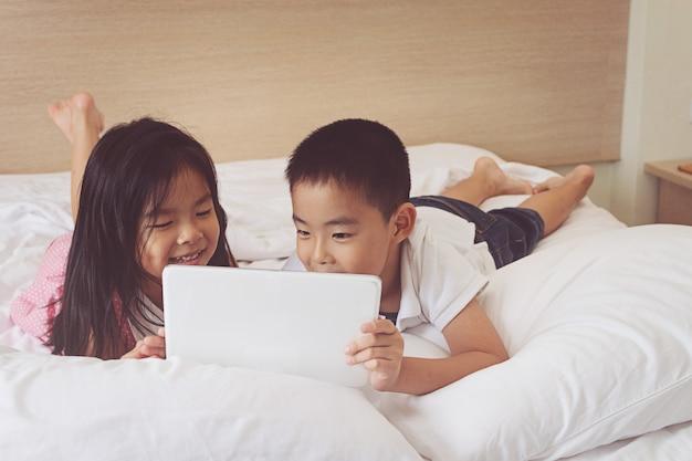 Asiatischer kleiner junge und mädchen, das tablet-computer im bett verwendet