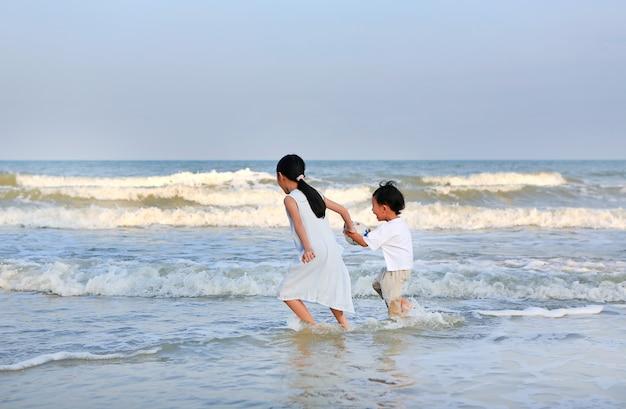 Asiatischer kleiner junge und mädchen, die sich im sommer am strand am meer amüsieren