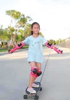 Asiatischer kleiner mädchen-skateboarder, der sicherheits- und schutzausrüstung trägt, die auf skateboard spielt. kinder-skateboarding auf der straße im freien