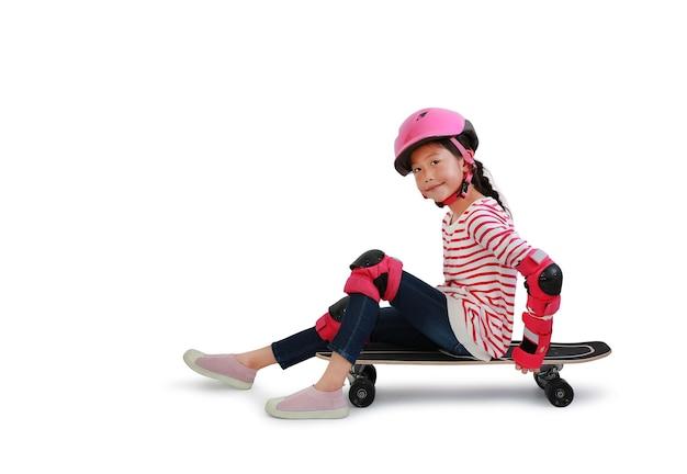 Asiatischer kleiner mädchen-skateboarder mit sicherheits- und schutzausrüstung, der auf dem skateboard sitzt, isoliert auf weißem hintergrund