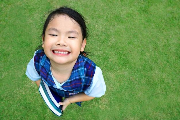Asiatischer kleiner netter mädchenkinderstudent in der einheitlichen grundschulehand, die ein buch und ein lächeln stehen auf schönem grünem park hält.
