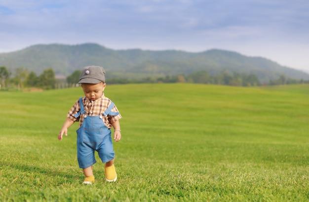 Asiatischer kleinkindjunge, der im naturpark spielt