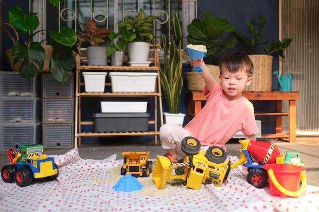 Asiatischer kleinkindjunge, der mit kinetischem sand zu hause spielt, kind, das mit spielzeugbaumaschinen spielt, montessori-ausbildung, kreatives spiel für kinderkonzept