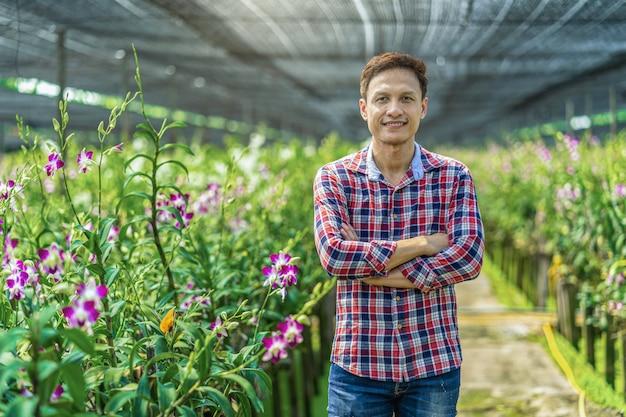 Asiatischer kleinunternehmer des porträts des orchideengartenbaubauernhofs, die purpurroten orchideen blühen im gartenbauernhof, glückgründer sind die gekreuzten arme, purpurrote orchideen in der landwirtschaft von bangkok, thailand.