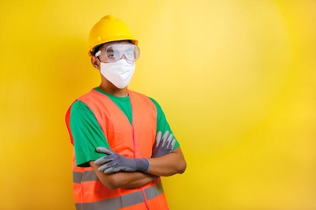 Asiatischer konstrukteursarbeiter mit maske und schutzbrillenstand kreuzte den arm mit vertrauensgeste vor gelbem hintergrund
