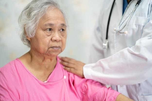 Asiatischer krankenschwester-physiotherapeut-arzt, der asiatische senioren oder ältere alte frauenpatientinnen mit liebe, sorgfalt, hilfe, ermutigung und empathie auf der krankenstation berührt, gesundes, starkes medizinisches konzept.