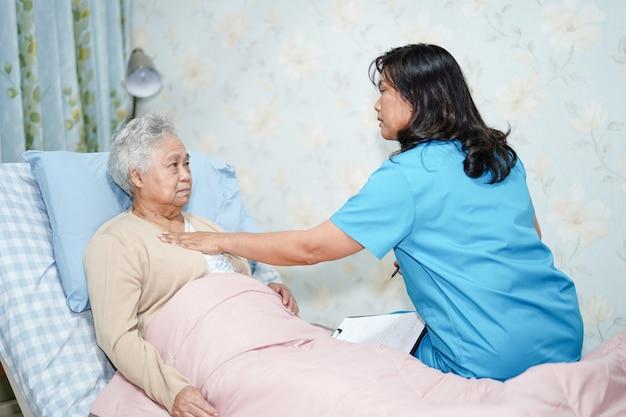 Asiatischer krankenschwesterdoktor stützen älteren frauenpatienten.