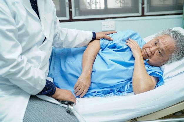 Asiatischer krankenschwesterphysiotherapeut, der alten patienten mit liebe und sorgfalt berührt.