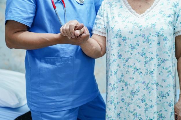 Asiatischer krankenschwesterphysiotherapeutendoktor, der asiatischen älteren oder älteren frauenpatienten alter dame mit liebe berührt