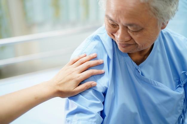 Asiatischer krankenschwesterphysiotherapeutendoktor, der asiatischen senior berührt