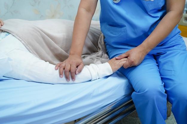 Asiatischer krankenschwesterphysiotherapist behandeln, helfen und unterstützen älteren frauenpatienten der alten dame.