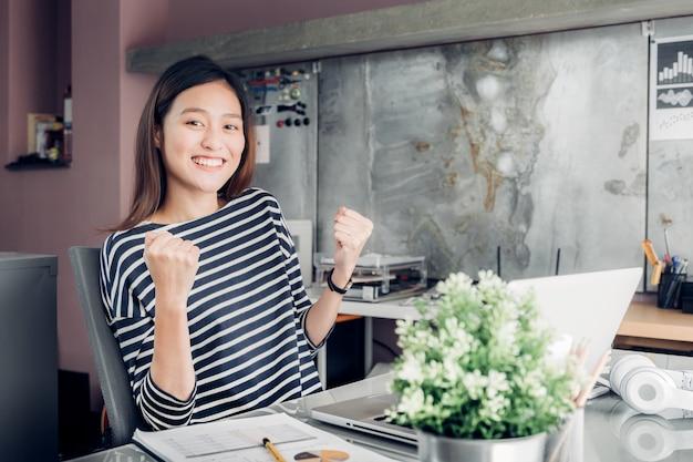 Asiatischer kreativer designer überreicht erfolg mit lächelndem gesicht über geschäftsvertrag