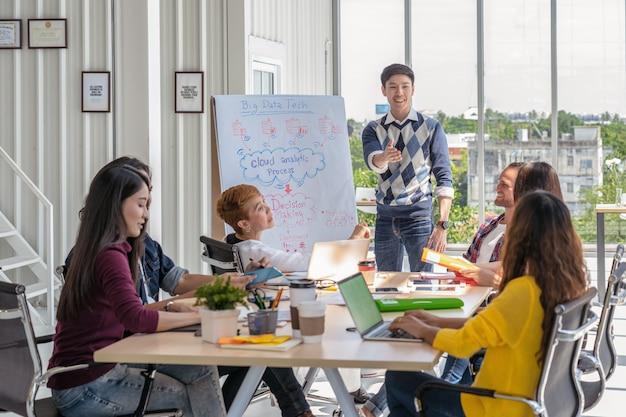 Asiatischer kreativer managermann, der die erfolgreichen ideen vor gruppe von asiatischem busi darstellt