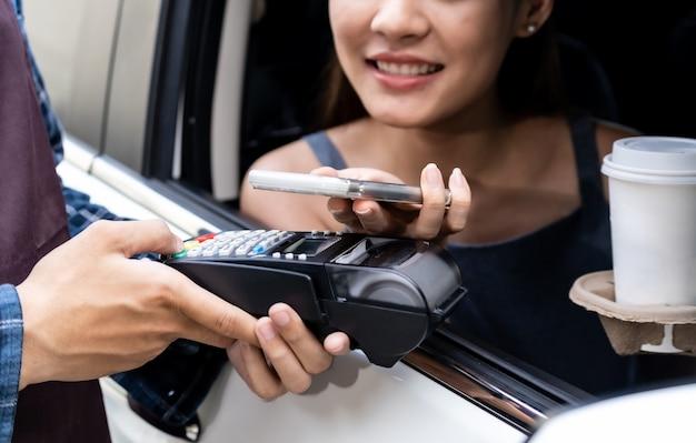 Asiatischer kunde macht kontaktloses mobiles bezahlen durchfahren