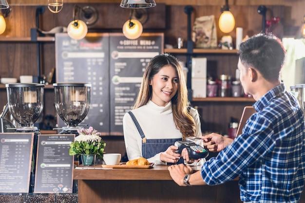 Asiatischer kundenmann, der mit kreditkarte über kontaktlose nfs-technologie an asiatischen barista bezahlt