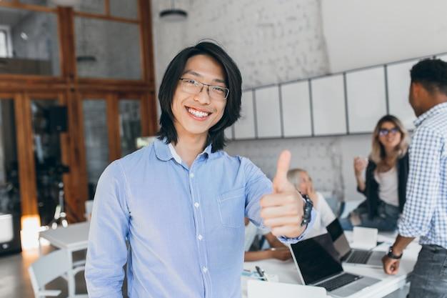 Asiatischer lachender junge, der mit daumen oben zu beginn des arbeitstages aufwirft. chinesischer büroangestellter im blauen hemd und in den gläsern, die mit laptop lächeln.