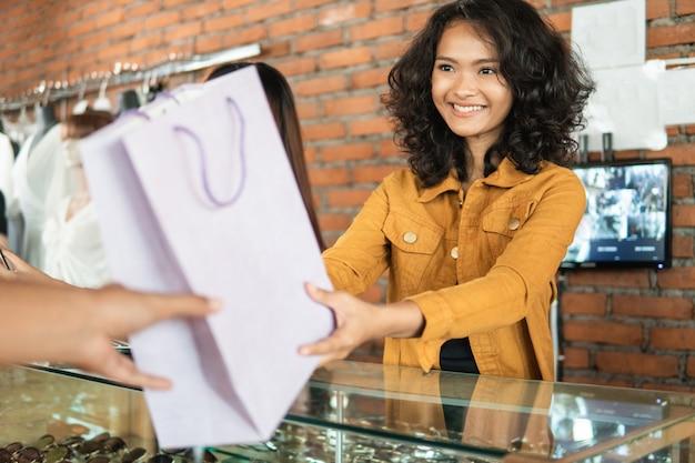 Asiatischer ladenbesitzer der frau, der einkaufstasche gibt