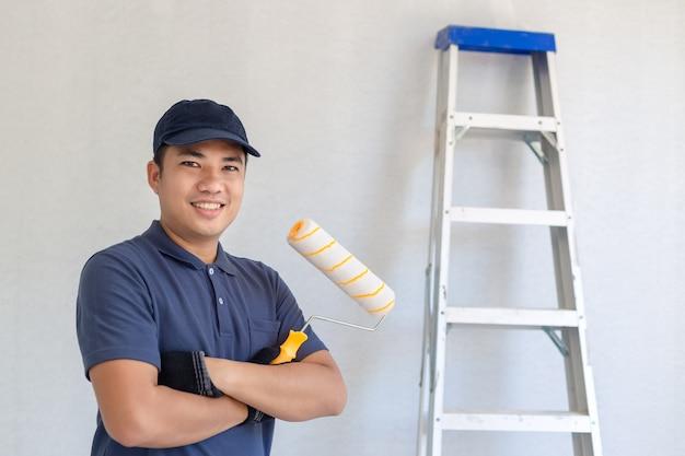 Asiatischer lächelnder maler, der eine farbenrolle und -hintergrund hält, hat eine aluminiumleiter.