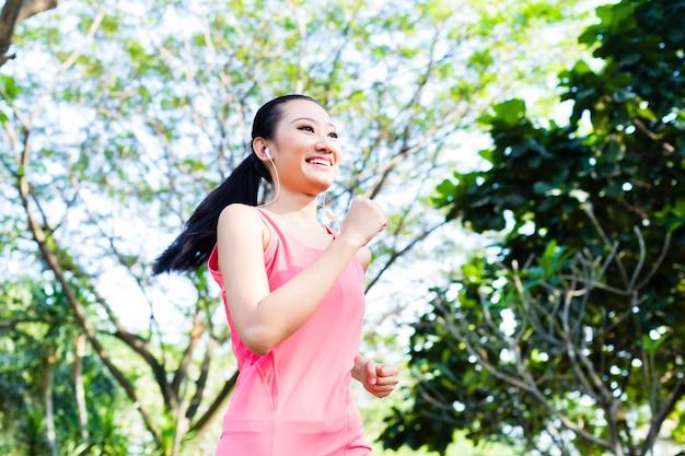Asiatischer läufer, der im stadtpark joggt