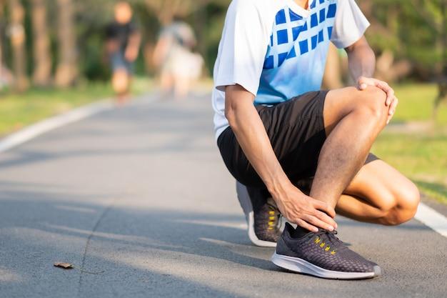 Asiatischer läufer, der knöchelschmerz und -problem nach dem laufen und übung draußen hat