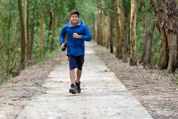 Asiatischer läufer in der sportklage laufen mit der glückaktion, die das wasser trinkt